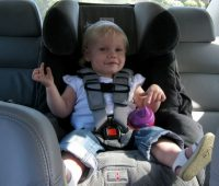 smiling child on car seat