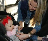 mom fixing baby on a car seat