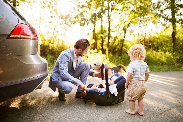 young-father-with-baby-and-toddler-by-the-car