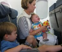 Baby, toddler, and a mother on a plane