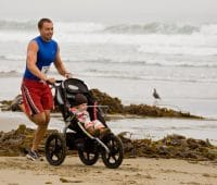father running a marathon with baby in a stroller